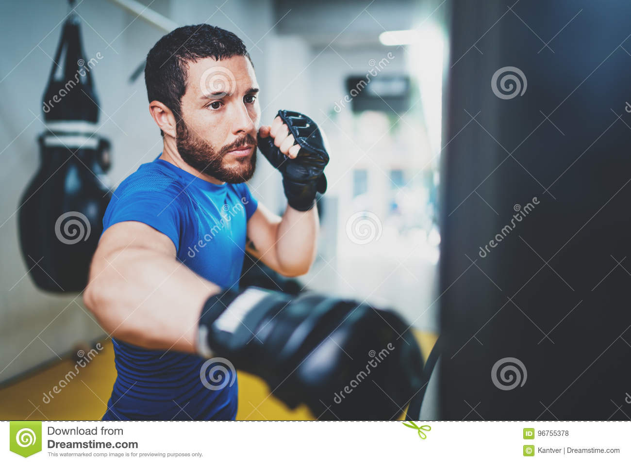 Young muscular kickboxing fighter practicing kicks with punching bag.Kick boxer boxing as exercise for the fight.Boxer