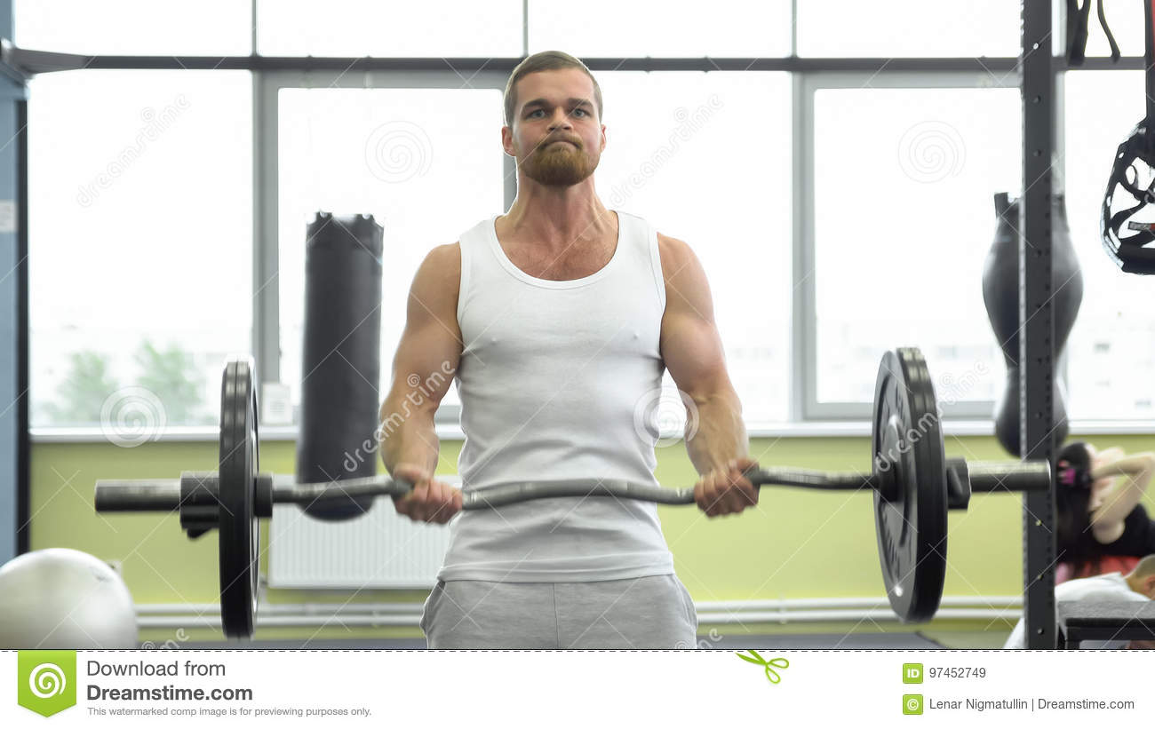 Athlete doing exercise for biceps with barbell. young muscular man trains at the gym. crossfit training