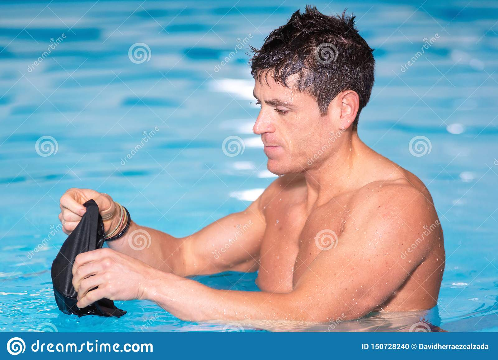 Young muscular swimmer preparing to swim, putting his cap on.