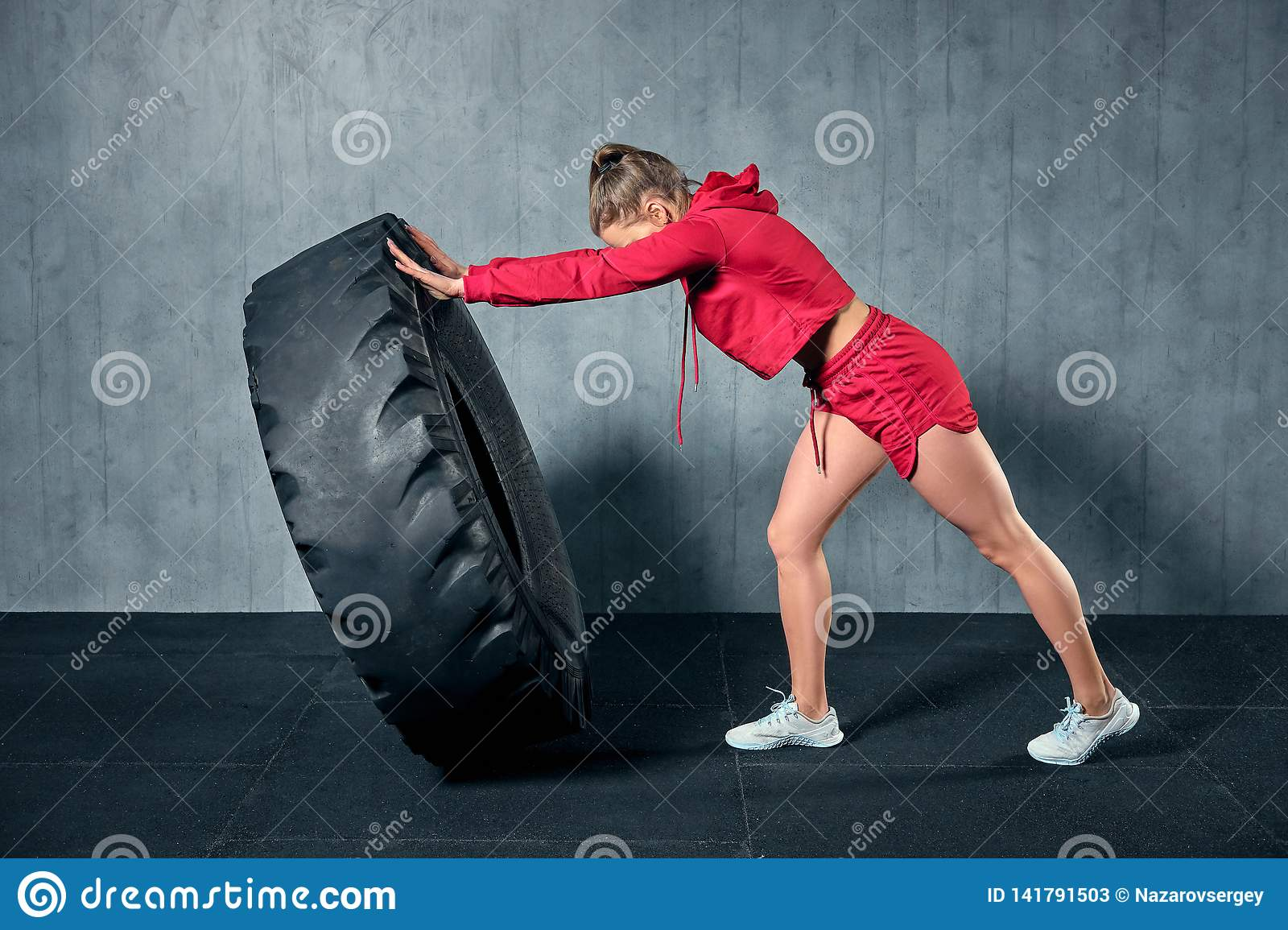 Young muscular woman flipping a tire on hard training with personal trainer at the garage gym.