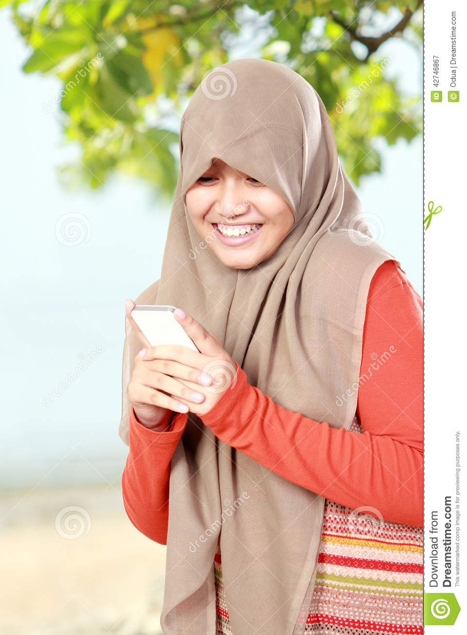 Cute smiling young girl holding a cell phone text a message