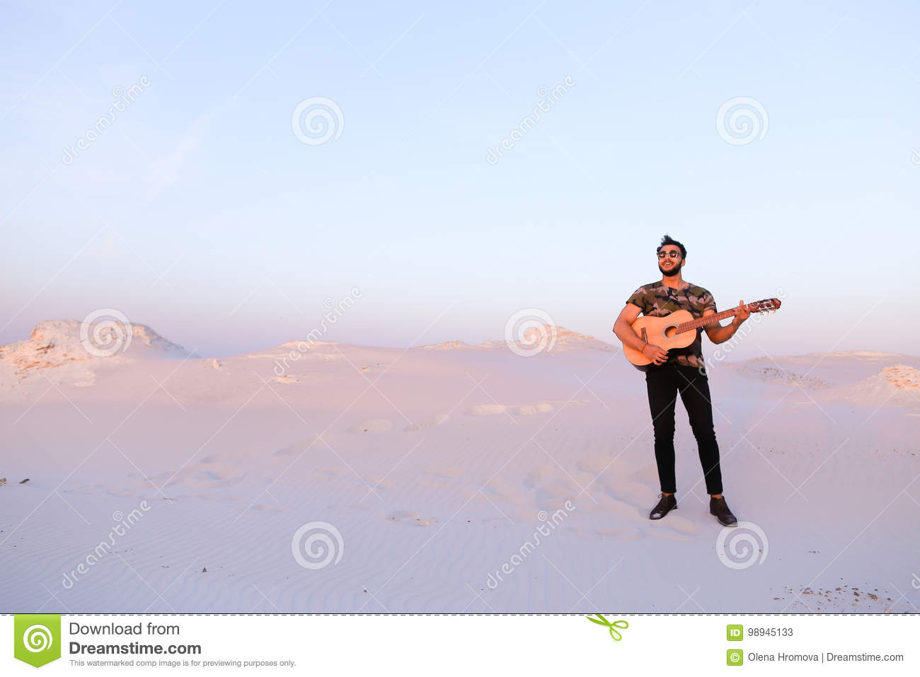 Handsome Male Arab Playing Guitar Standing In Middle Of Bottomle