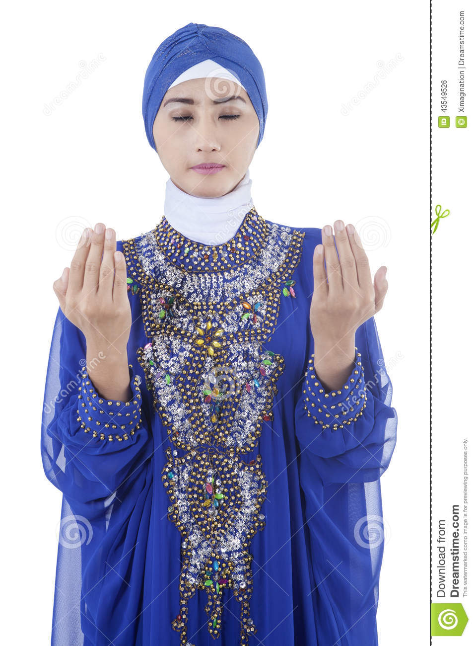 Pretty young muslim woman wearing islamic clothes and praying