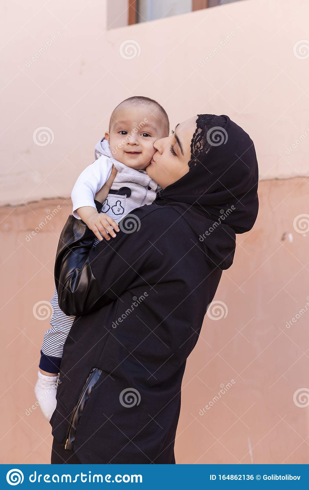 Young Muslim Woman In Hijab Holding Her 1-year-old Baby