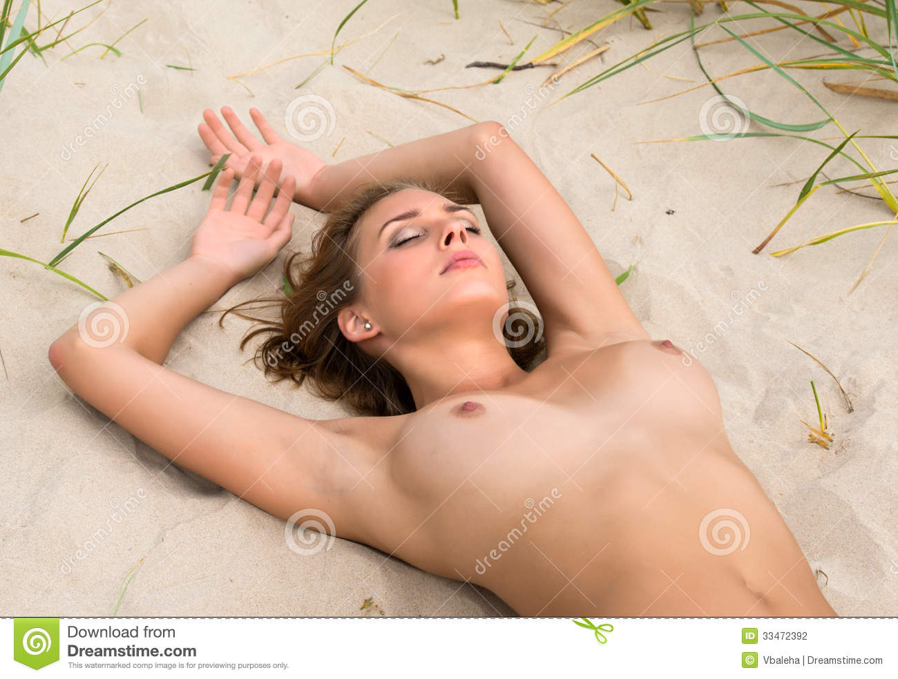 Young Naked Woman Sunbathing On The Beach