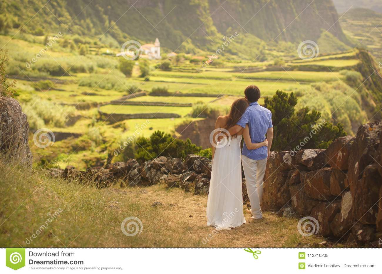Young newly wedded hugging couple in honneymoon on Flores island, Azores