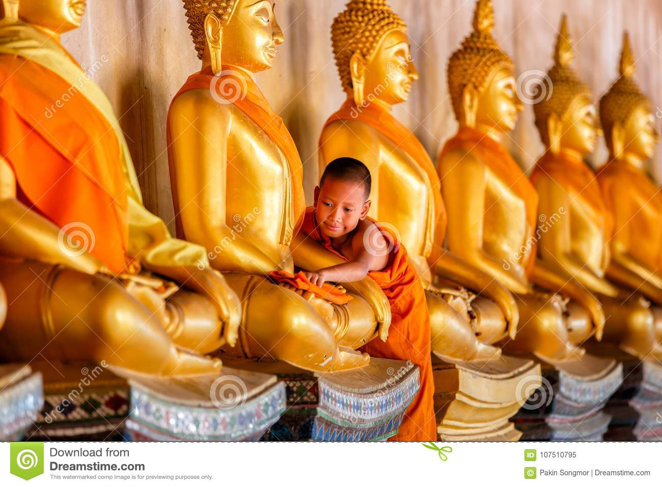Young Novice monk scrubbing buddha statue at old temple in thailand