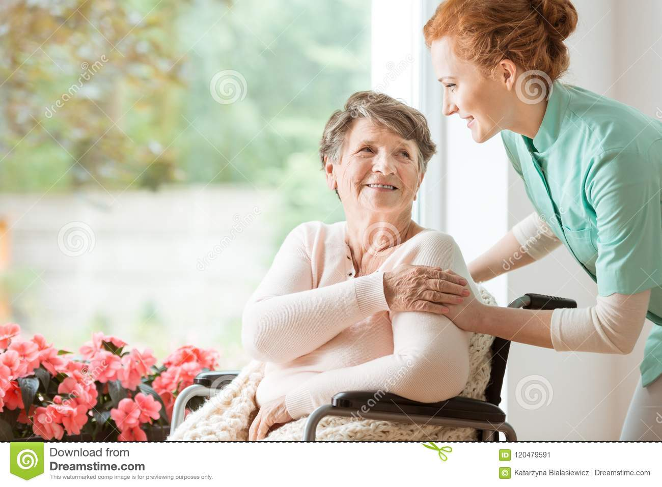 Young nurse helping an elderly woman in a wheelchair. Nursing ho
