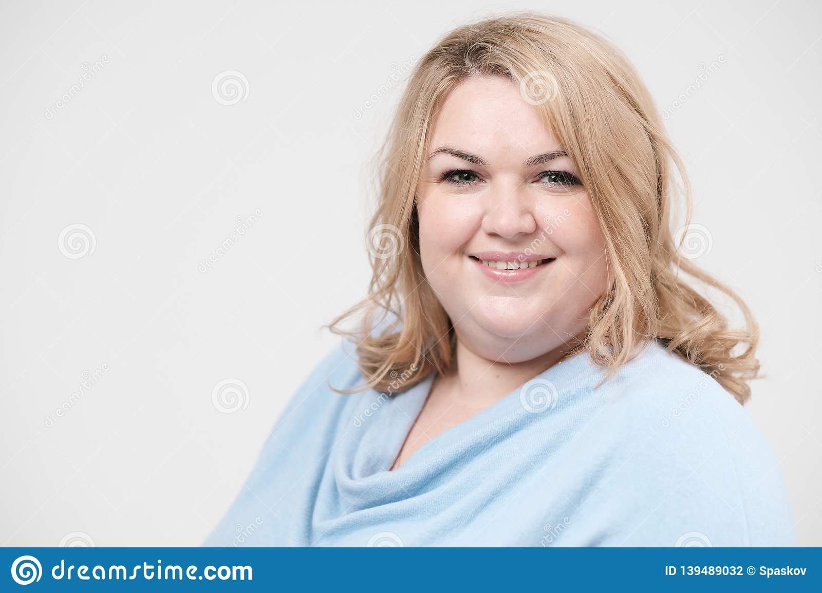 Young obese woman in casual blue clothes on a white background in the studio. Bodypositive.