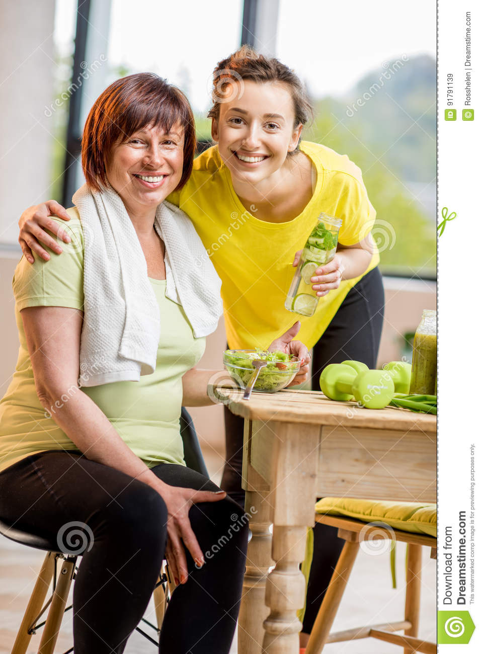 Young And Older Women Exercising With Dumbbells And Eating Healthy Food Indoors On The Window Background