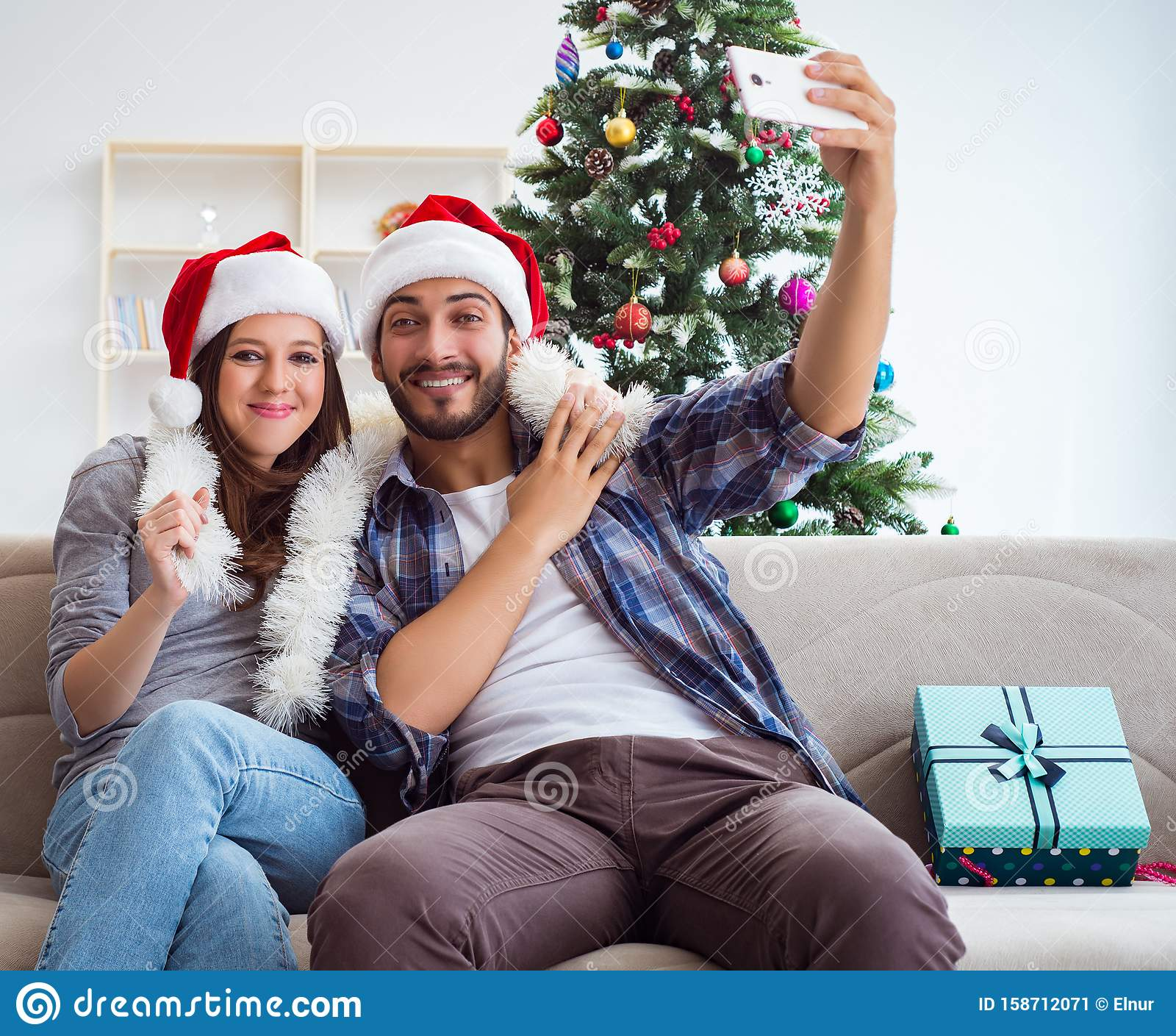 Young pair taking selfies during christmas