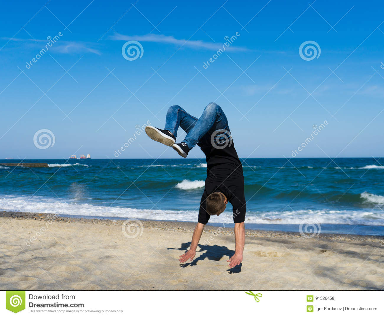 0b2770ff33a6eb Portrait of young parkour man doing flip or somersault on the beach.  Freezed moment of flip.