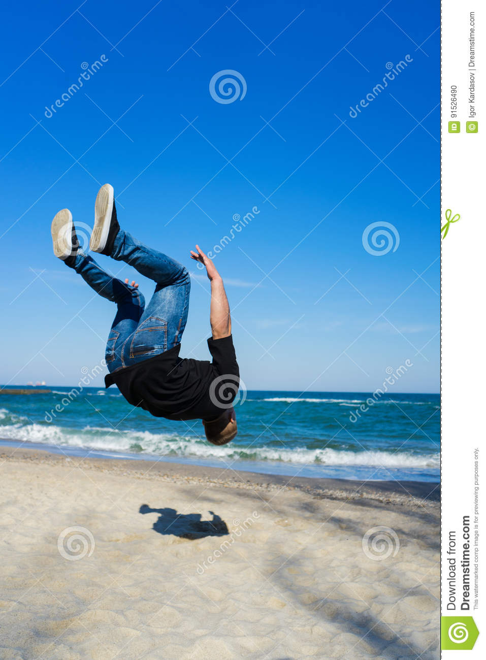 ae8d7b5655fd23 Portrait of young parkour man doing flip or somersault on the beach.  Freezed moment - finishing of flip