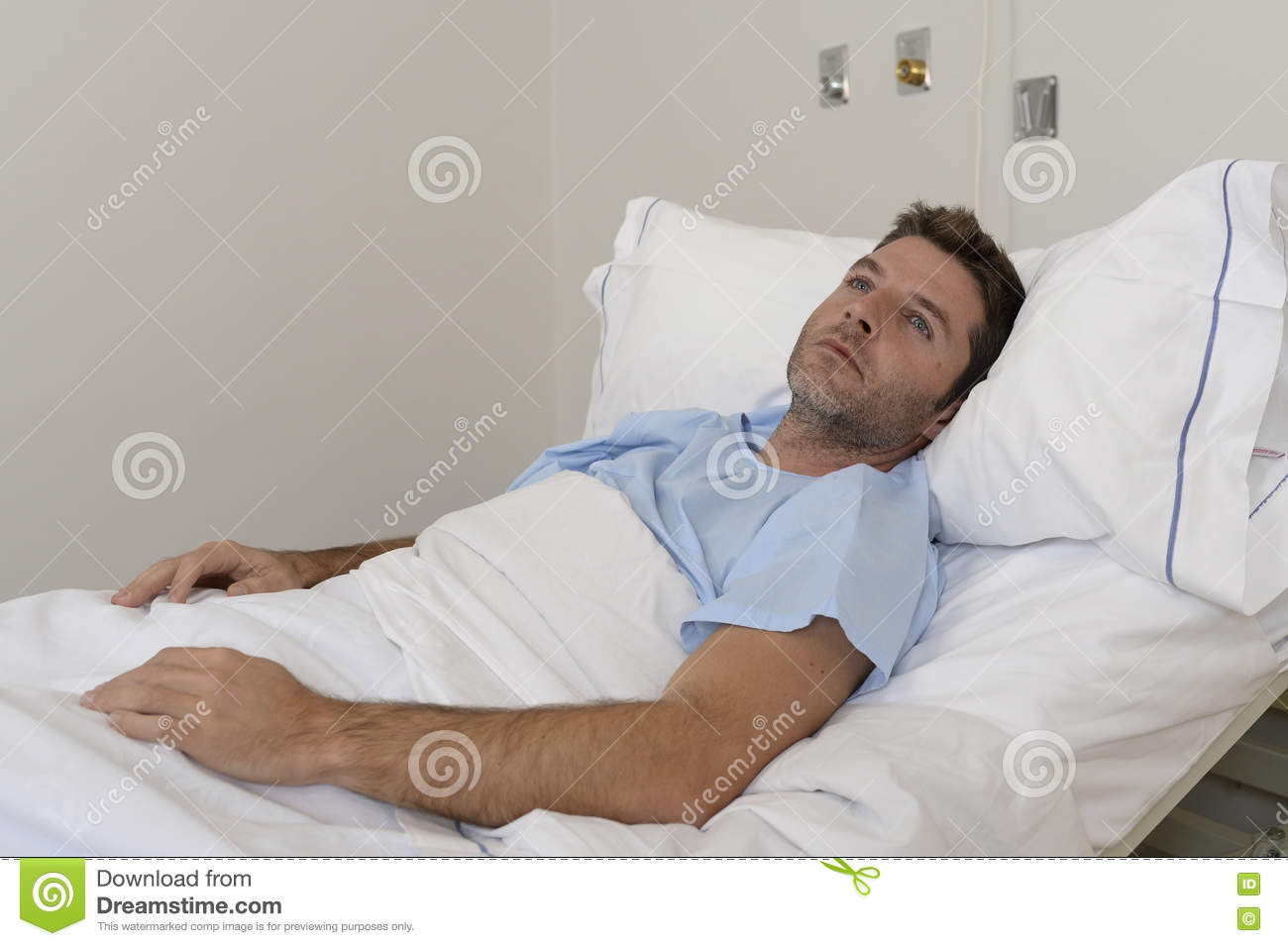 Young patient man lying at hospital bed resting tired looking sad and depressed worried