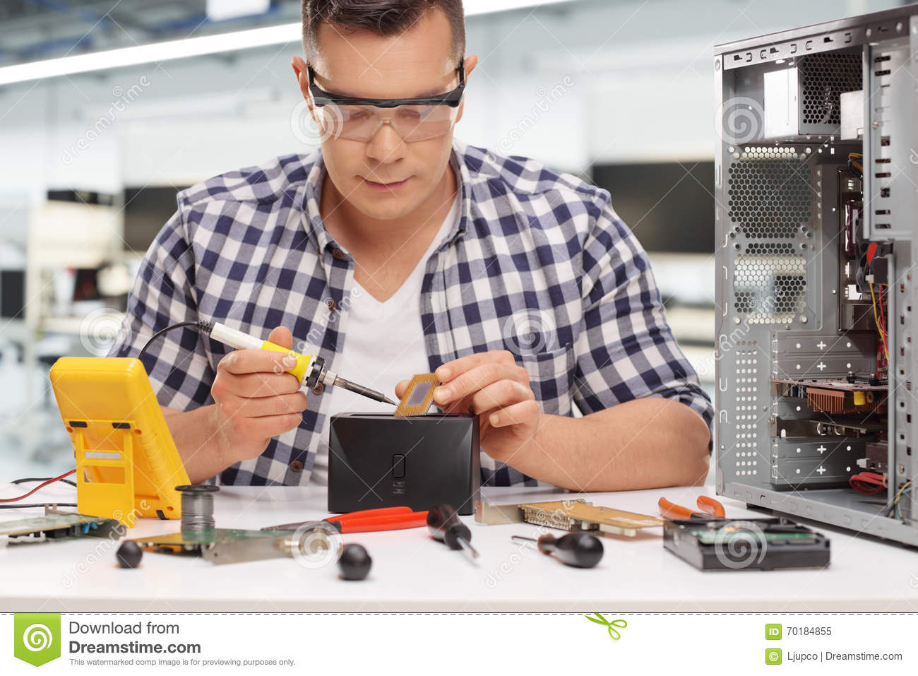 young pc technician soldering a chip stock photo image 70184855. Black Bedroom Furniture Sets. Home Design Ideas