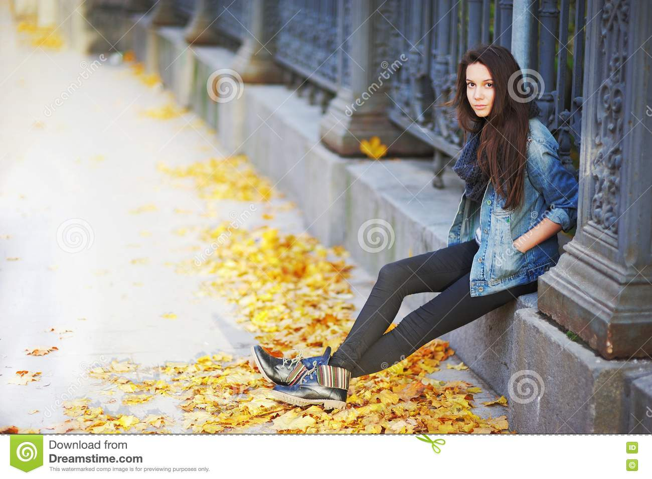 Young Pensive Brunette Girl Sitting On A Concrete Curb