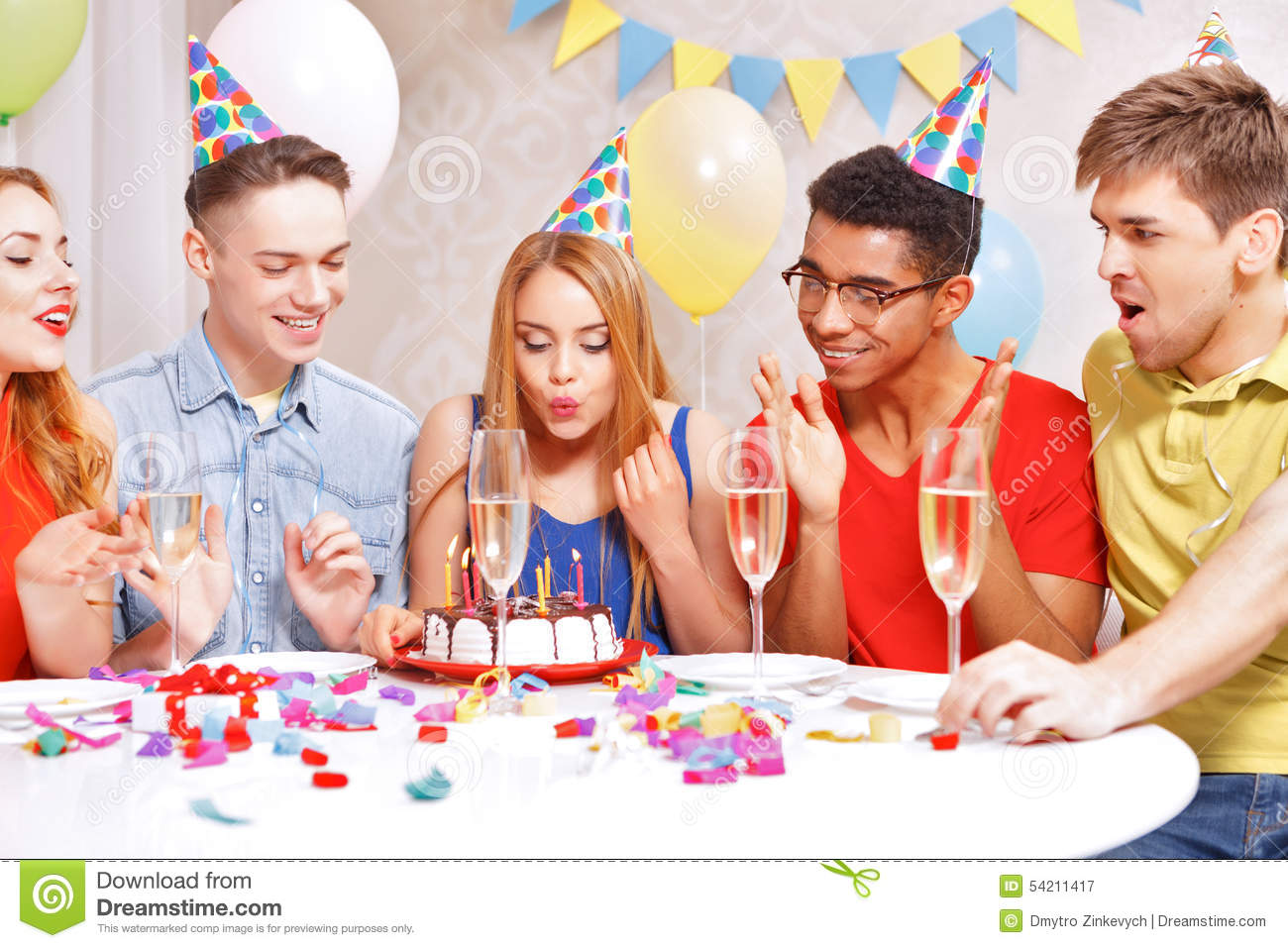 Young people celebrating a birthday sitting at the