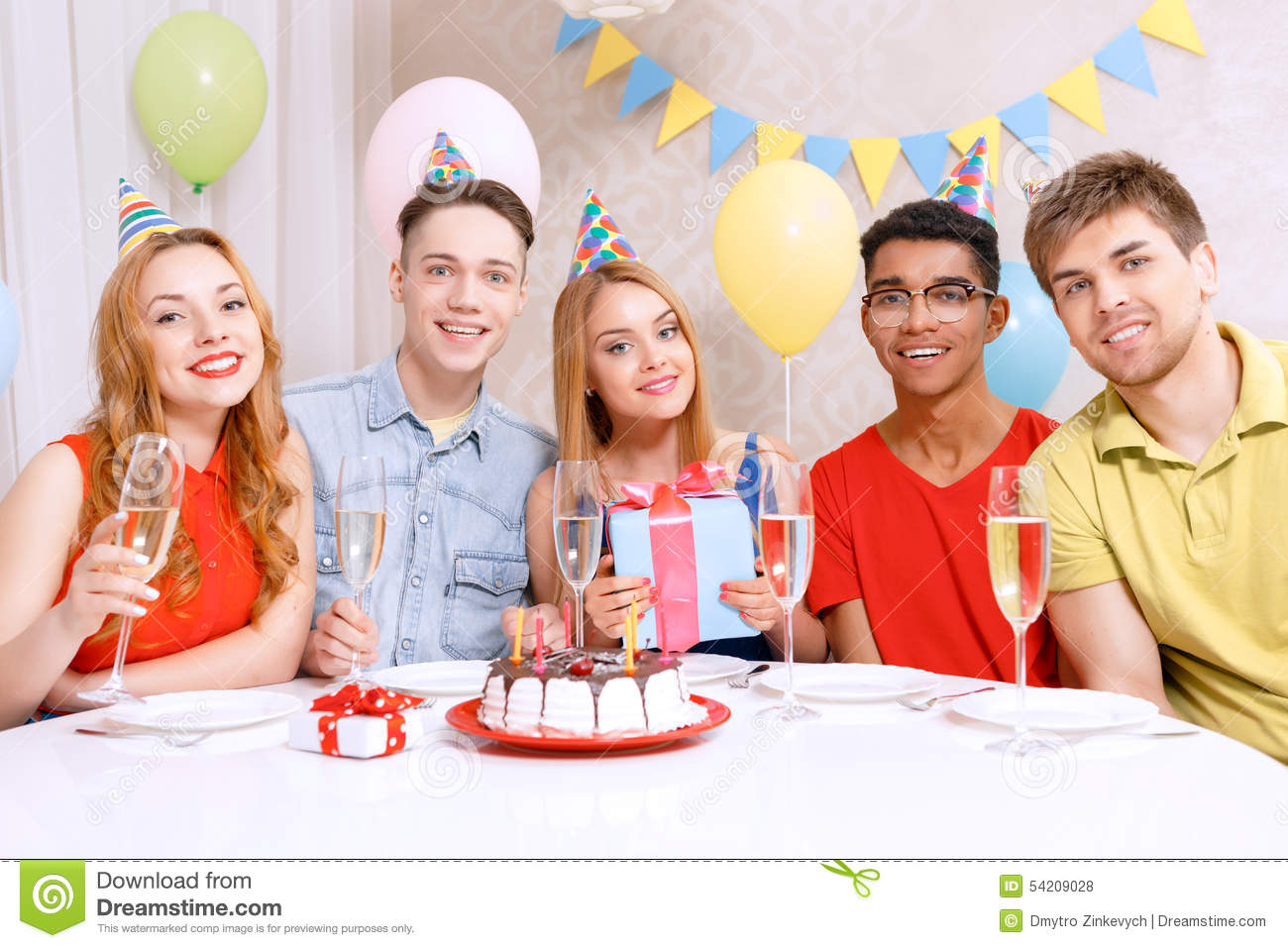 People Sitting At Table With Birthday Cake