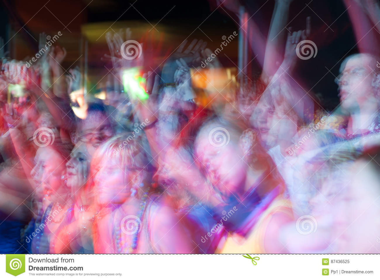 Young people crowd dancing and cheering during a rock band music concert performance at a festival