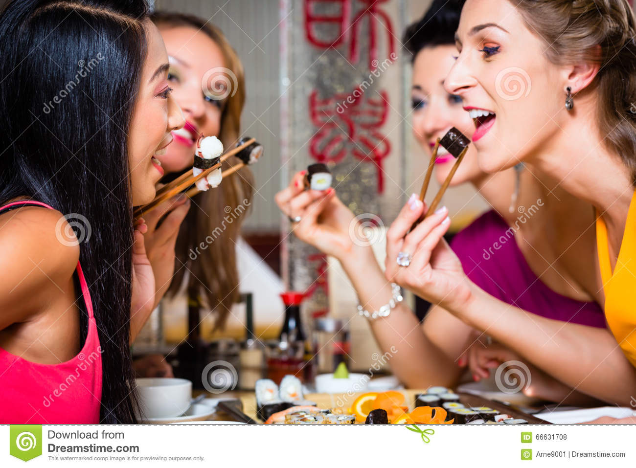 Young people eating sushi in restaurant