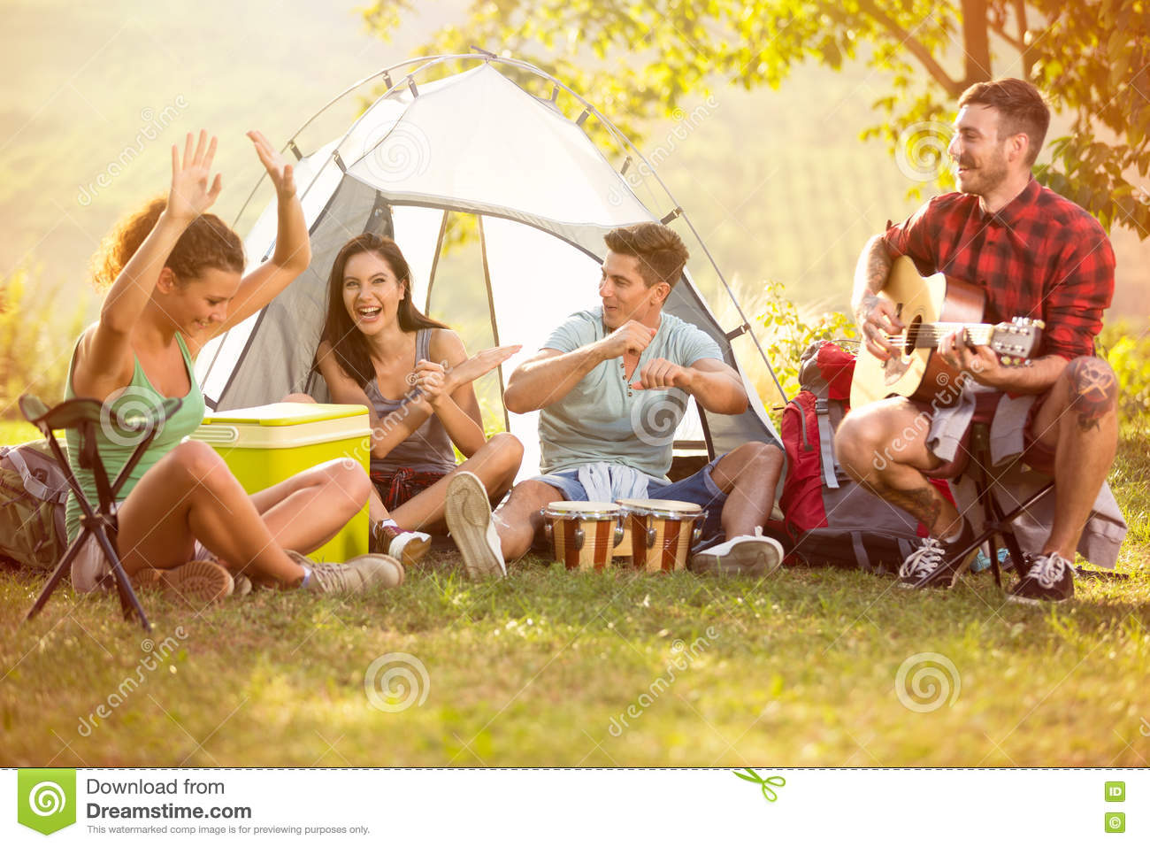 Young people enjoy in music of drums and guitar on camping trip
