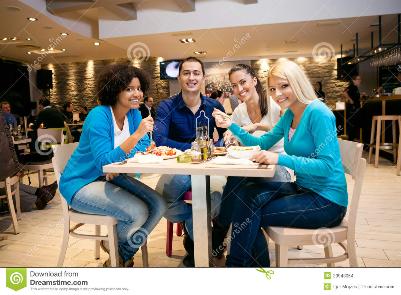 Young people having lunch in restaurant stock images for Group lunch