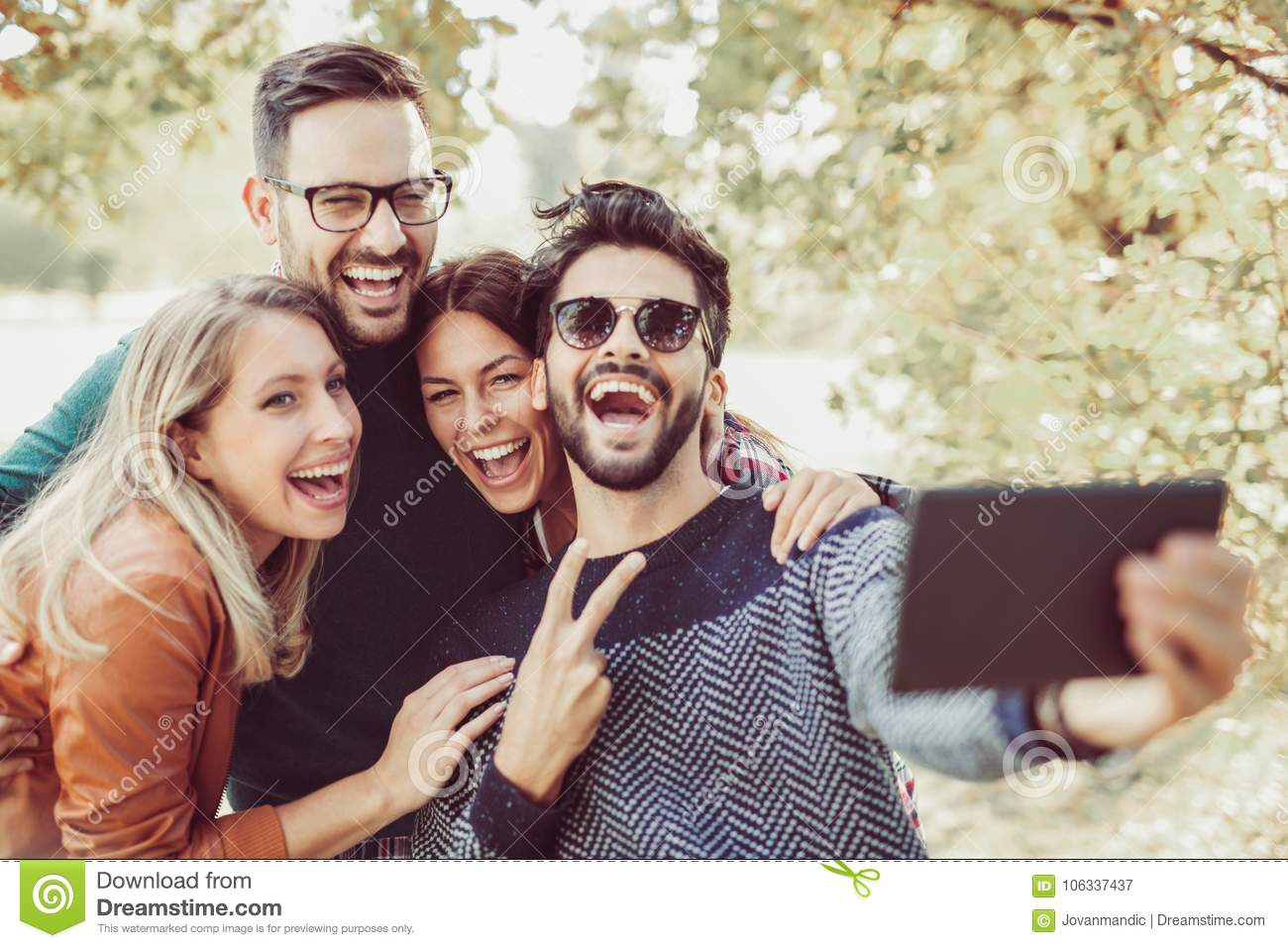 Young people in park with digital tablet having fun