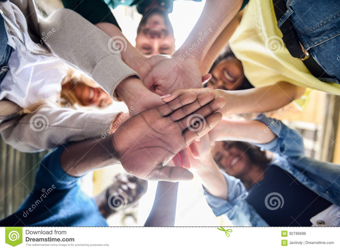 Young people putting their hands together.
