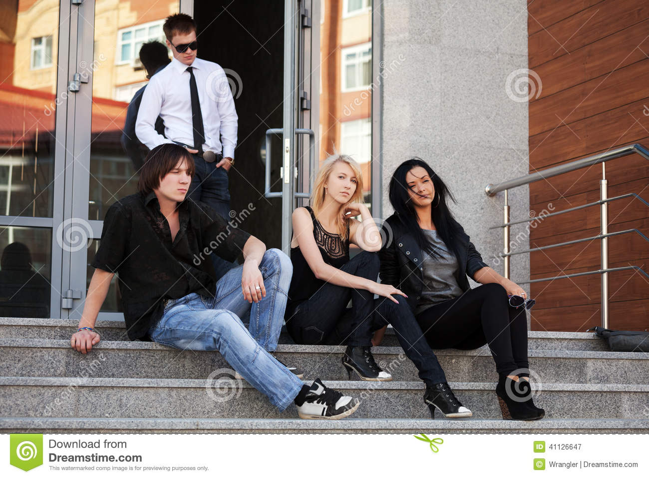 Young fashion people sitting on the steps