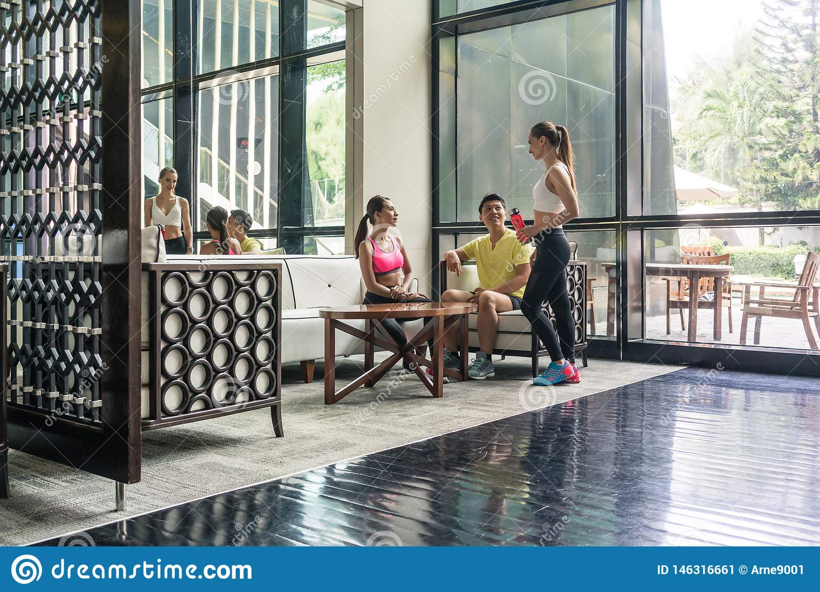Young people socializing in the lounge area of a trendy health club