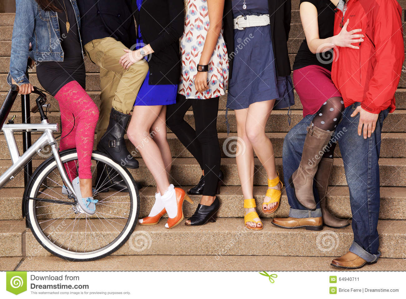 7 young people on stairs, with a bicycle.