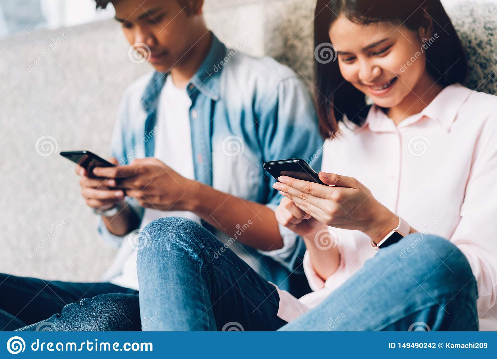 Young people are using smartphone and smiling while sitting on free time. technology concept.