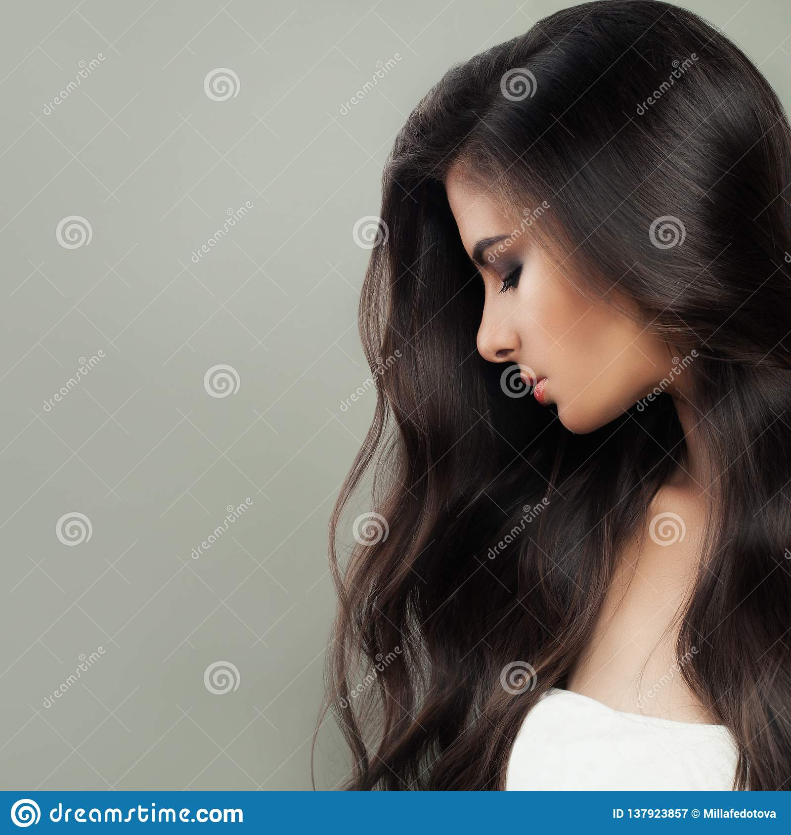 Young perfect brunette woman portrait. Long dark healthy hair and natural makeup. Hair care concept
