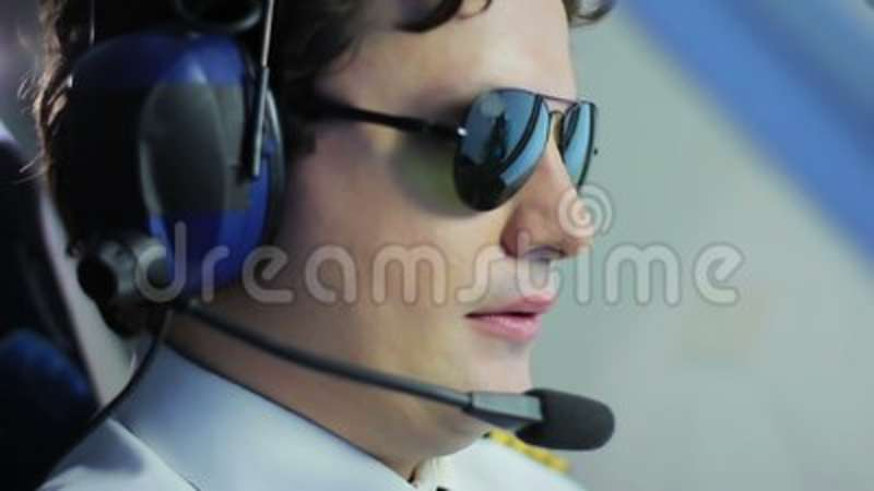 4004c5df5a Young Pilot Wearing Sunglasses And Steering Airliner
