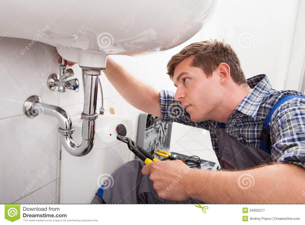 Young Plumber Fixing A Sink In Bathroom Royalty Free Stock