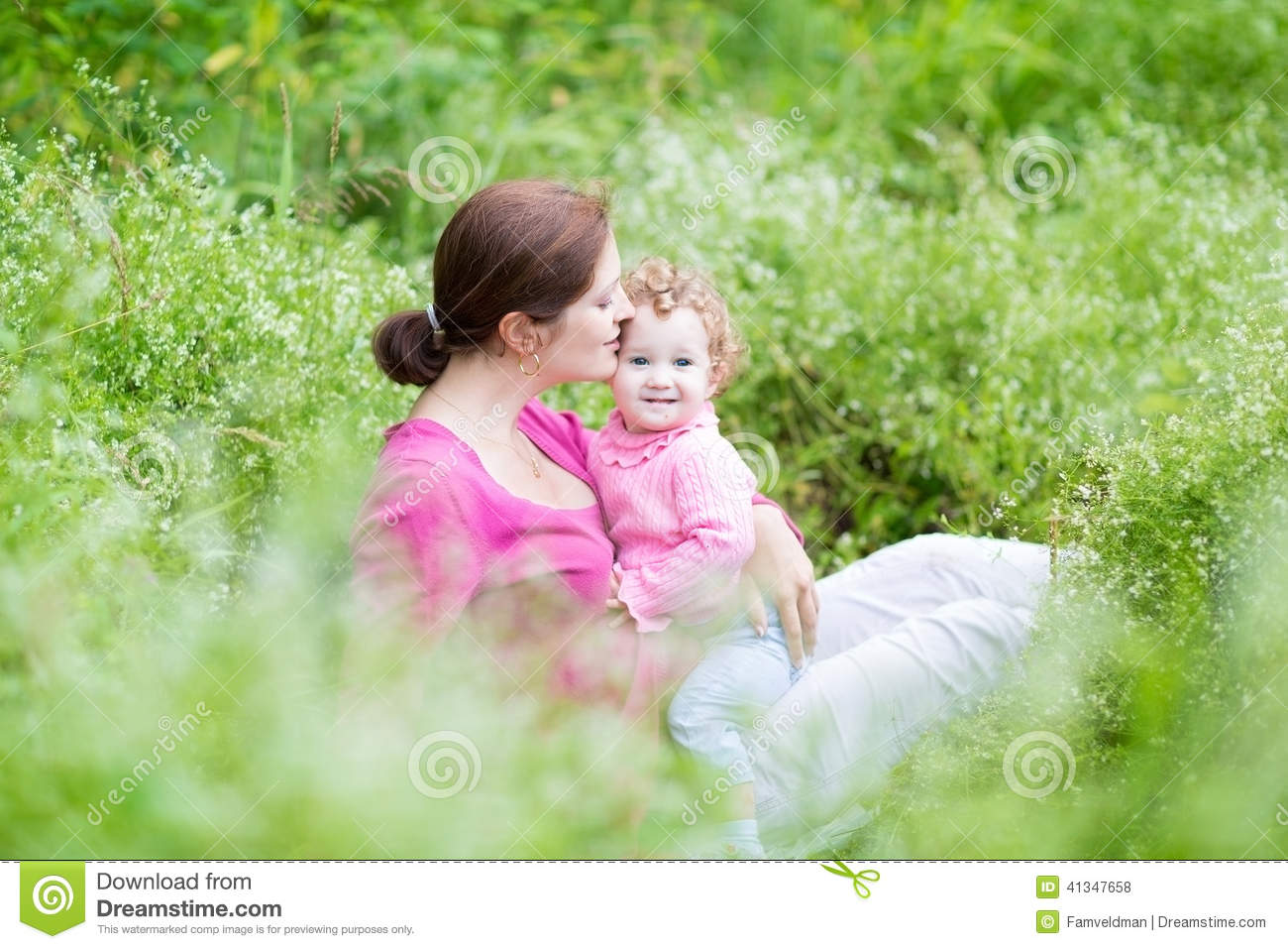Young pregnant mother and her baby daughter in garden for Gardening while pregnant