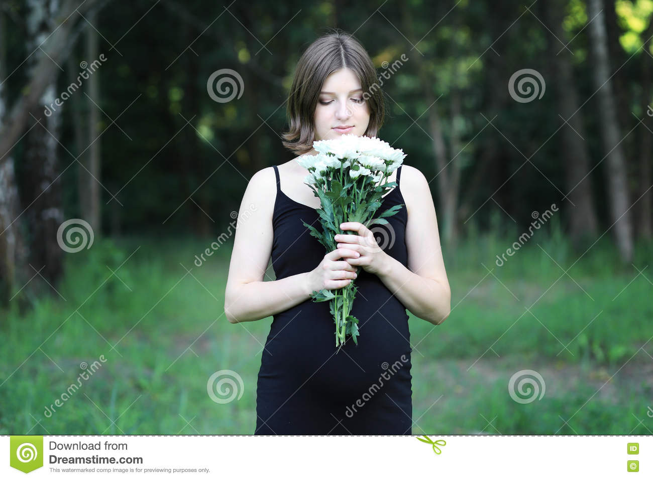 Young Pregnant Woman Is In The Black Dress With White Flowers Stock