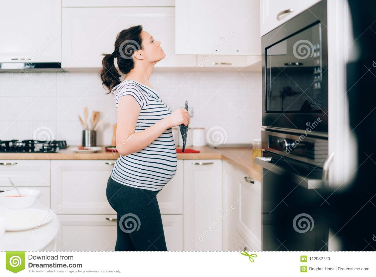 Young pregnant woman cooking in her kitchen standing and looking in cabinets near stove