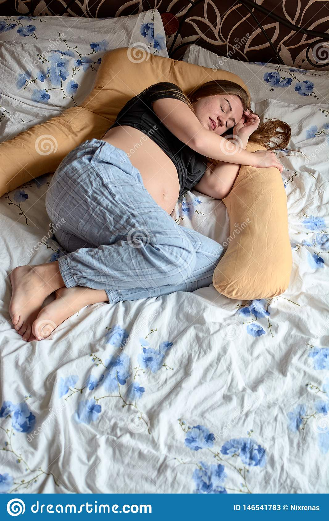 Young pregnant woman. Pregnant beautiful woman sleeps on maternity pillow in bed