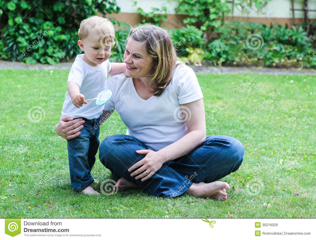 Pregnant woman and little son in summer garden royalty for Gardening while pregnant