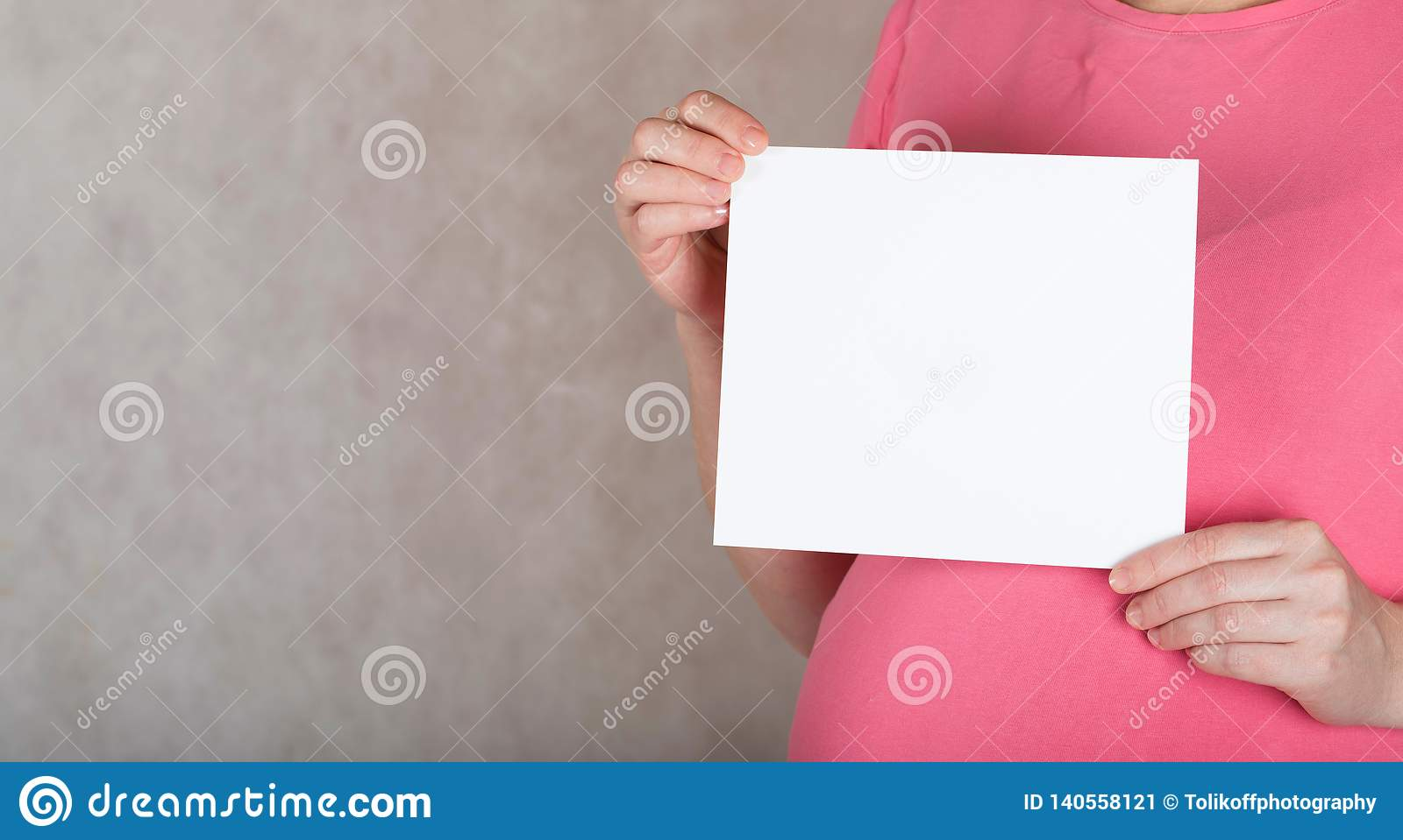 Young pregnant between 30 and 35 years old woman keeps a blank white sheet of paper
