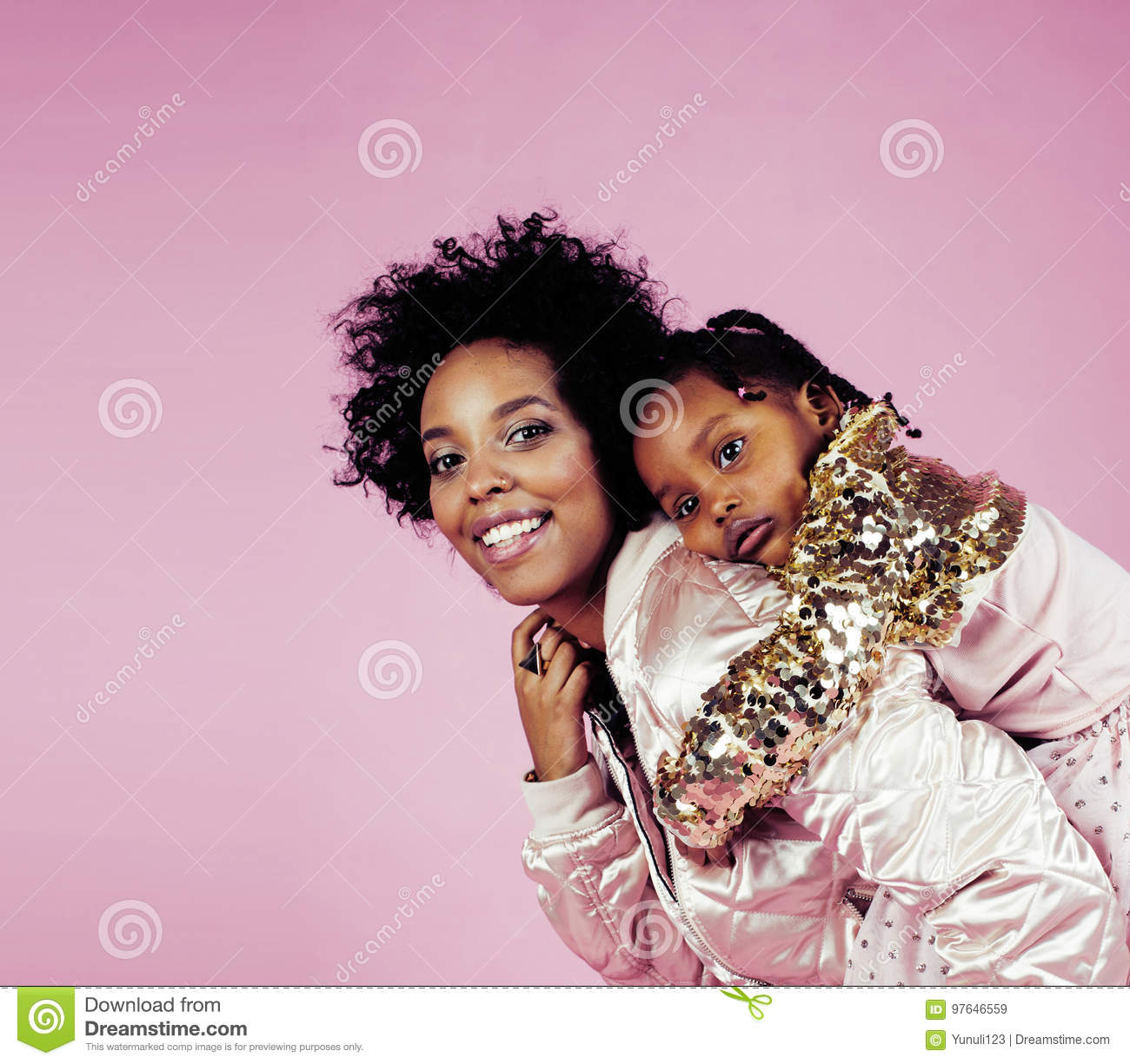 Young pretty african-american mother with little cute daughter hugging, happy smiling on pink background, lifestyle