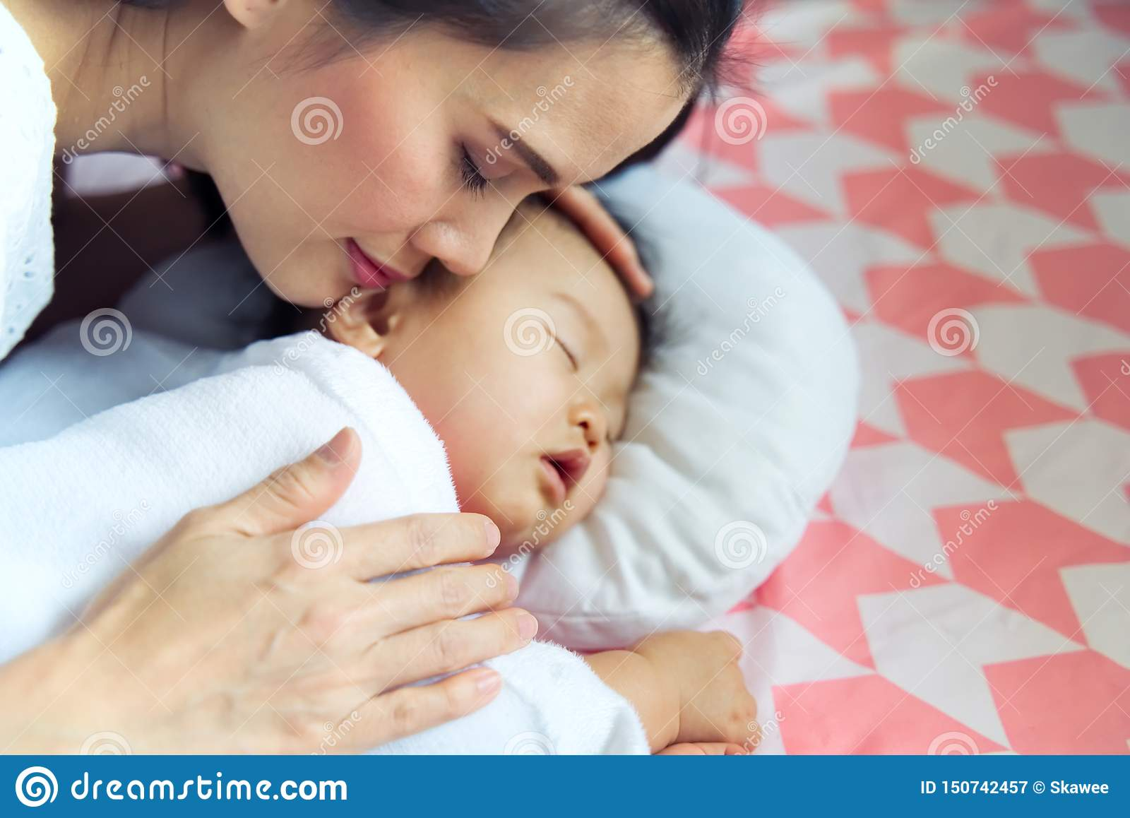 Young pretty Asian mother hugging her sleeping cute baby on the bed. The mother closing her eyes when touching her child softly