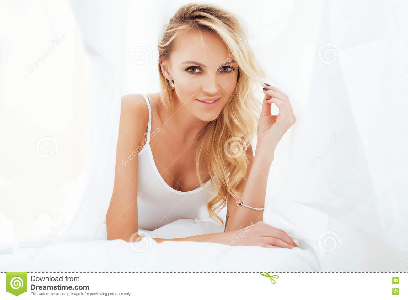 0b211e01b82b Young pretty blond woman in bed covered white sheets smiling cheerful look  close up