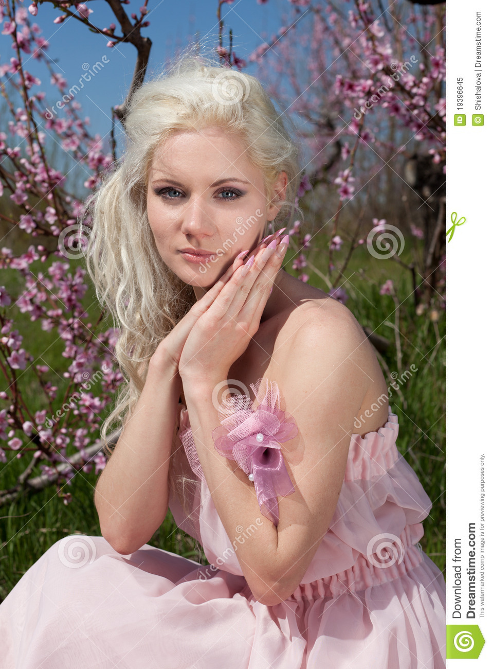 Young pretty blond woman in blooming garden