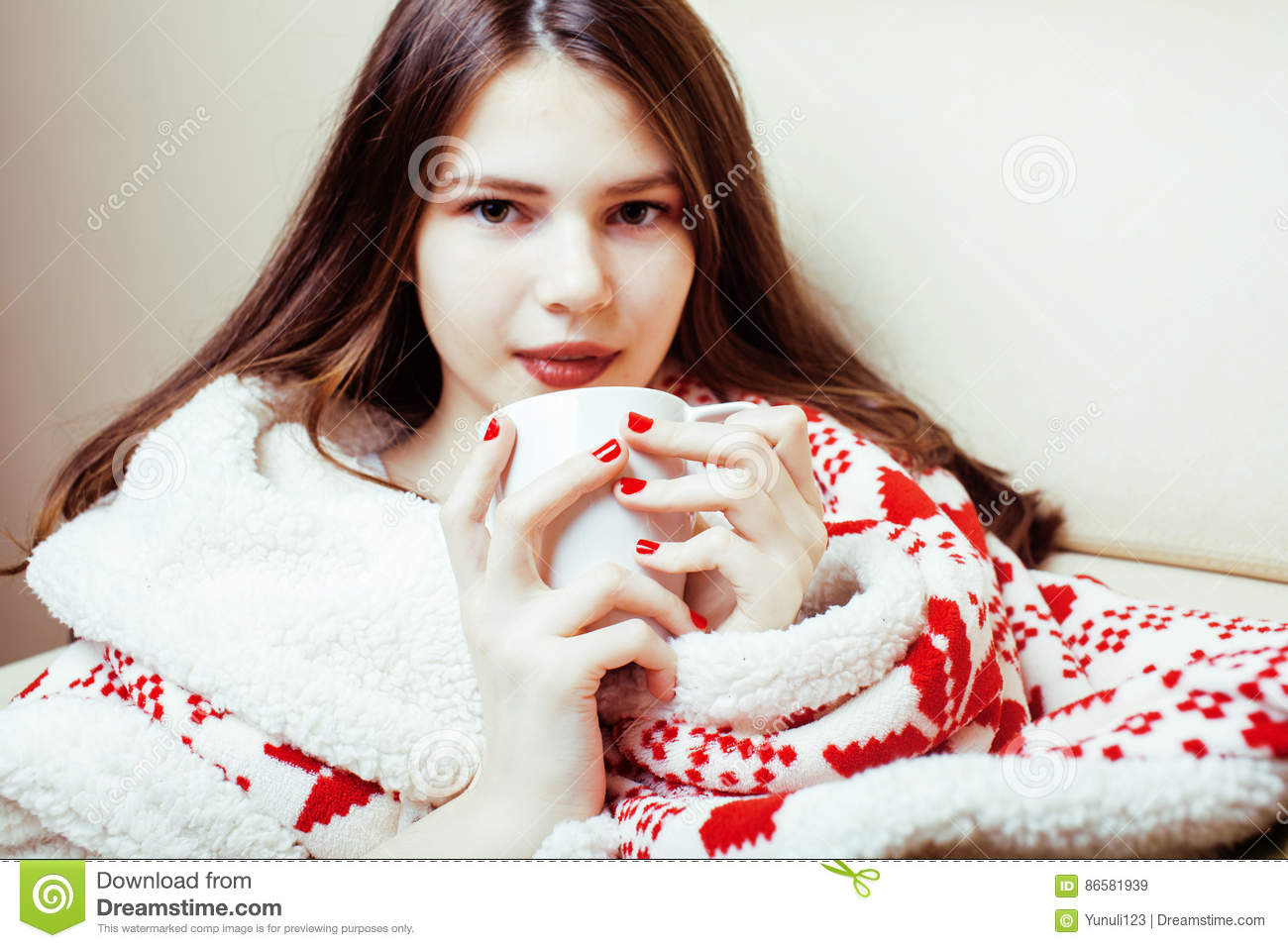 Young pretty brunette girl in Christmas ornament blanket getting warm on cold winter, freshness beauty concept