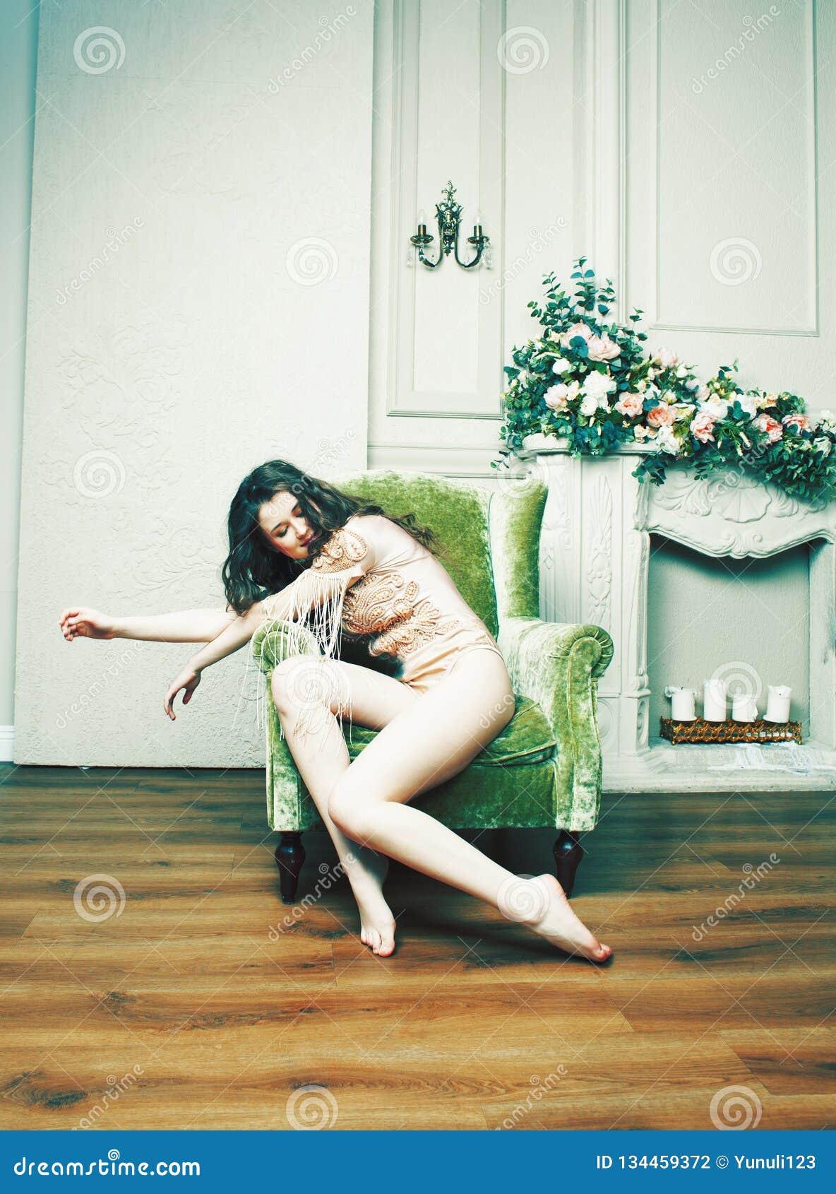 Young pretty brunette girl in fashion dress on sofa posing in lu