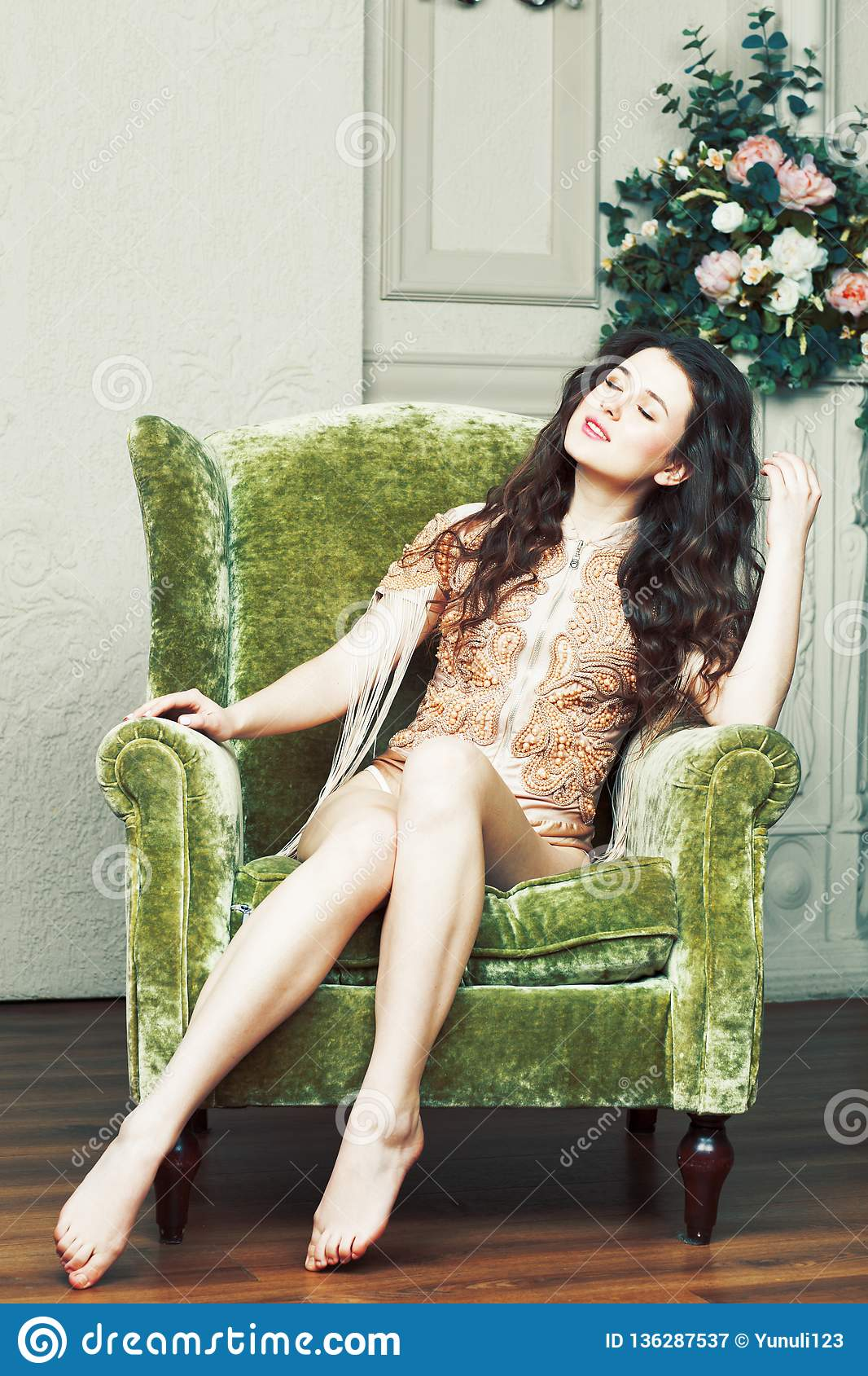 Young pretty brunette girl in fashion dress on sofa posing in lu