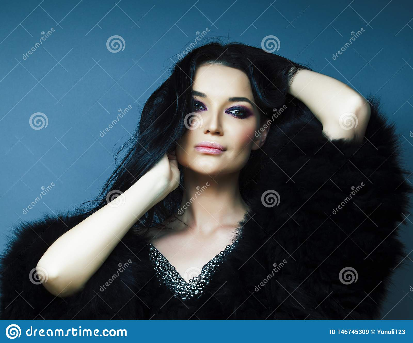 Young pretty brunette girl with fashion makeup posing elegant in fur coat with jewelry on blue background, lifestyle