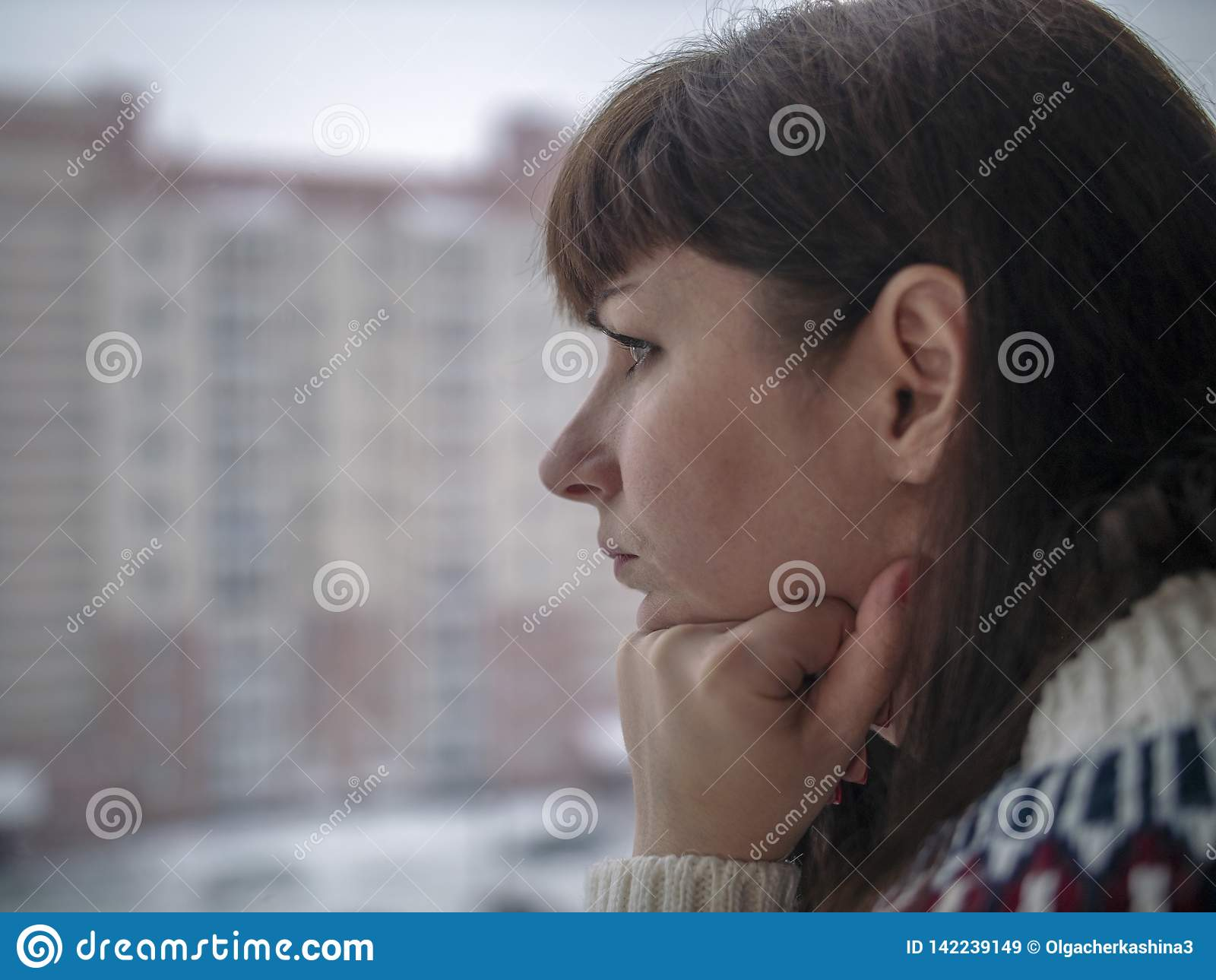 Young pretty brunette woman with long hair looks thoughtfully while standing at the window close-up
